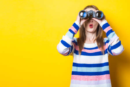 Young woman with a surprised face looks through binoculars on a yellow background. Banner.