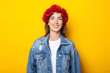 Young woman with a smile in a denim jacket and a wreath of red flowers on her head on a yellow background.