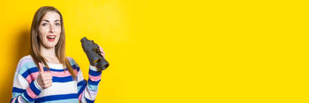 Young woman with a smile makes a welcome gesture and holds binoculars in her hands on a yellow background. Banner. Reklamní fotografie