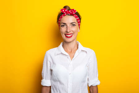 Young woman with a headband smiling on a yellow background. Banner.