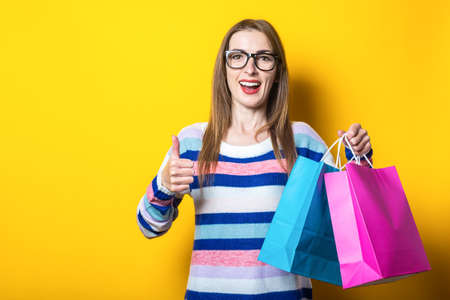 Young woman smiles and makes a gesture all is well, holds and shopping bags with purchases on a yellow background. Banner.
