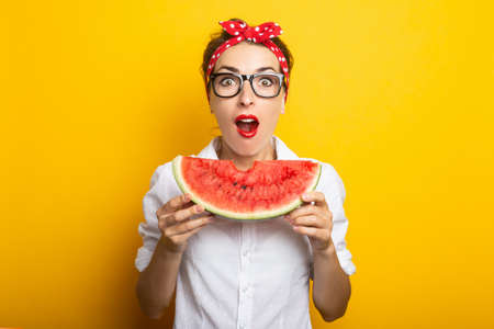 Young woman with a surprised face in a red headband and glasses eats a watermelon on a yellow background. Reklamní fotografie