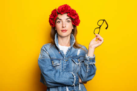 Young woman in a denim jacket and a wreath of red flowers on her head holds glasses on a yellow background.