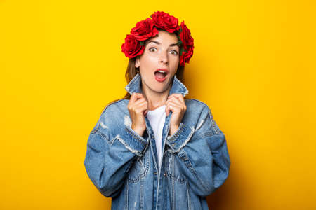 Young woman with a surprised face in a denim jacket and a wreath of red flowers on her head on a yellow background.