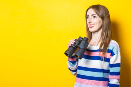 Young woman with a smile holds binoculars in her hands on a yellow background. Banner. Reklamní fotografie
