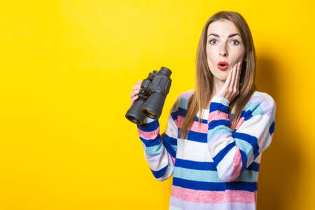 Young woman with a surprised face holds binoculars on a yellow background. Banner.