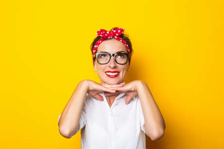 Young woman with a smile, wearing glasses and a red headband on her head on a yellow background. Reklamní fotografie