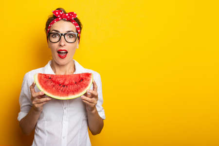 Young woman with surprised face with red headband and glasses holding a piece of watermelon on yellow background. Reklamní fotografie