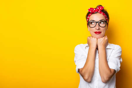 Young woman holds her hands on her chin, wearing glasses and a headband on a yellow background. Banner. Reklamní fotografie
