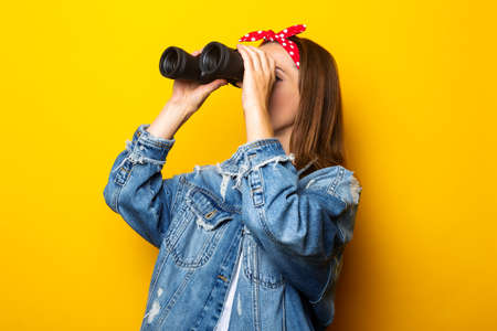 Young woman in a denim jacket and a raft on her head looks through binoculars on a yellow background. Banner.