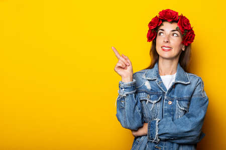 Young woman with a smile looks to the side in a denim jacket and a wreath of red flowers on her head on a yellow background.