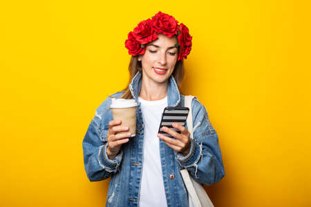 Young woman in a denim jacket and a wreath of red flowers on her head holds a paper cup with coffee and a phone on a yellow background.