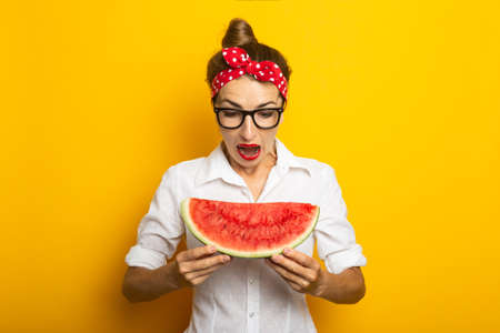 Young woman with a smile in a red headband and glasses eats watermelon on a yellow background.