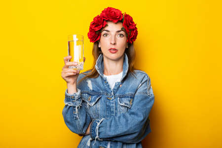 Young woman in denim jacket and a wreath of red flowers on her head holding a glass of water on a yellow background.