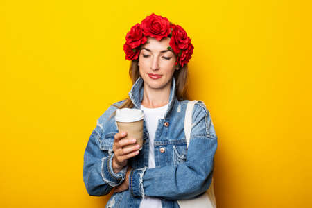 Young woman in a denim jacket and a wreath of red flowers on her head holds a paper cup with coffee and looks at it on a yellow background.