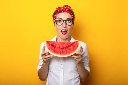 Young woman with a smile in a red headband and glasses holds a watermelon on a yellow background.