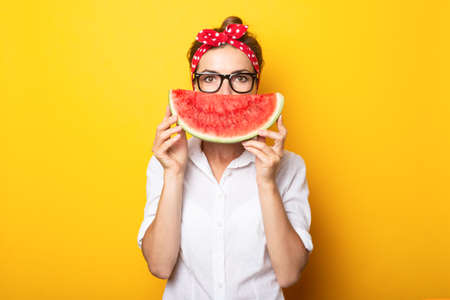 Young woman in a red headband and glasses covers half of her face with watermelon on a yellow background.