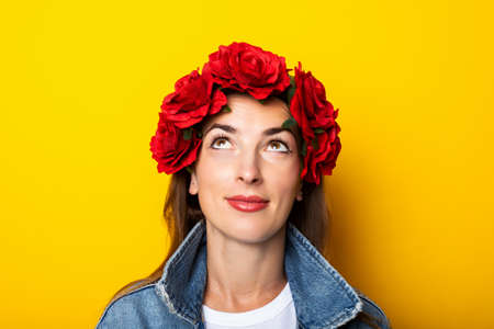 Young woman looks up in a denim jacket and a wreath of red flowers on her head on a yellow background.