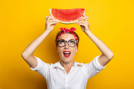 Young woman with surprised face with red headband and glasses holds watermelon above her head on yellow background. Reklamní fotografie