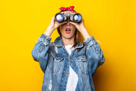 Young woman with a surprised face in a denim jacket and a raft on her head looks through binoculars on a yellow background. Banner.