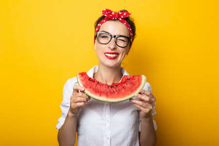 Young woman with a smile in a red headband and glasses eats a watermelon on a yellow background.