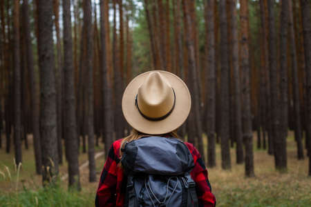 Young woman in hat, red shirt and backpack with in a pine forest. Camping in the woods.