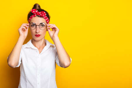 Young woman with a headband straightens her glasses on a yellow background. Banner. Reklamní fotografie