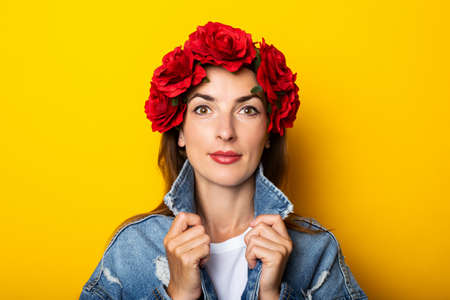 Young woman in denim jacket and a wreath of red flowers on her head on a yellow background.