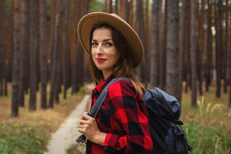 Young woman in hat, red shirt and backpack in the forest. Hike in the forest.