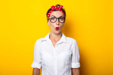 Young woman with a surprised face, wearing glasses and a headband on her head on a yellow background. Reklamní fotografie