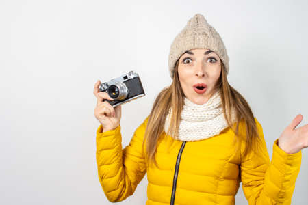 Young woman with a surprised face in a yellow down jacket and hat holds a camera in her hands on a light background. Concept of beauty and fashion, winter, autumn, technology. Banner.