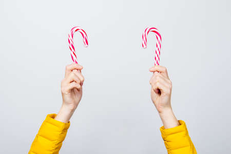 female hands holding two loli pop candies on a light background. Banner. Concept Christmas, New Year, Valentine's Day. 스톡 콘텐츠