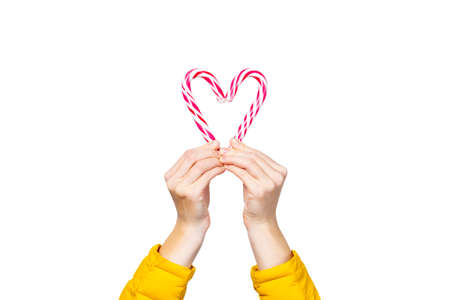female hands hold two lolipop candies, hold in the form of a heart on a white background. Concept Christmas, New Year, Valentine's Day.