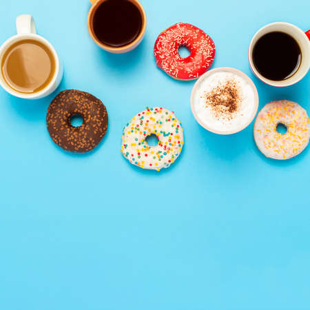 Tasty donuts and cups with hot drinks, coffee, cappuccino, tea on a blue background. Concept of sweets, bakery, pastries, coffee shop, meeting, friends, friendly team. square. Flat lay, top view. 免版税图像