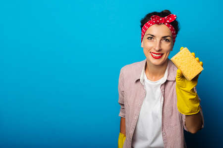 Smiling young woman in a hair band with gloves holding a sponge on a blue background