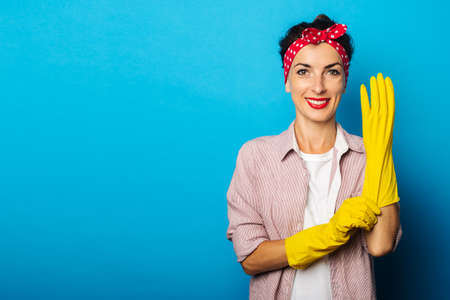 Smiling young woman in shirt puts on yellow gloves for cleaning on blue background