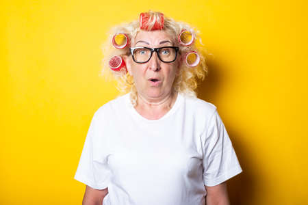 Surprised shock old woman with curlers in a white t-shirt on a yellow background.