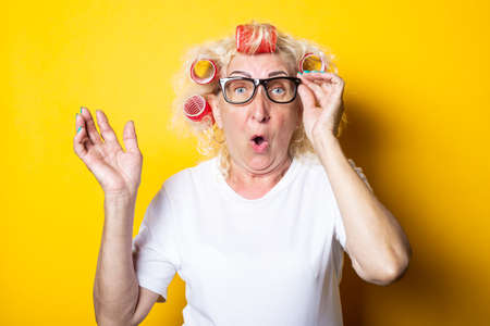 Surprised shock old woman with curlers in glasses looks to the side on a yellow background.