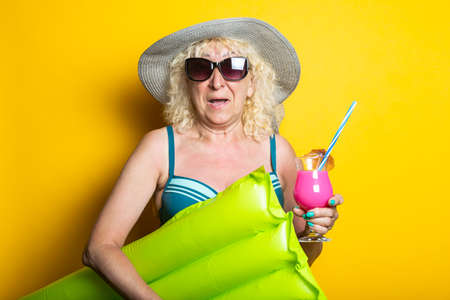 Happy old woman in swimsuit with cocktail holding air mattress on yellow background