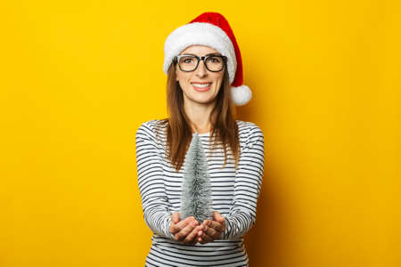 Young woman with a smile in a Christmas hat holds a beautiful Christmas tree on a yellow background. Banner.