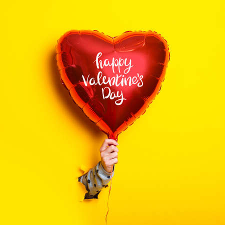 Female hand holds an inflatable balloon with the inscription Happy Valentines Day on a torn yellow background.
