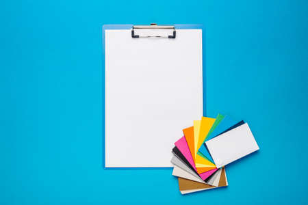 Color palette of paints and clipboard with blank paper for text on a light blue background. Banner. Top view, flat lay.
