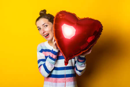 Young woman in a sweater hides behind an air balloon heart on a yellow background. Valentine's day composition.