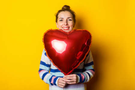 Young woman in a sweater holds an air balloon heart on a yellow background. Valentine's day composition. Stock fotó