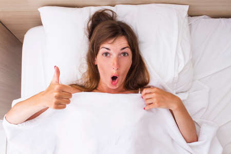 A young woman with a surprised face is lying in bed. Concept insomnia, dreams, sleeping pills, good sleep, good sex. Flat lay, top view.