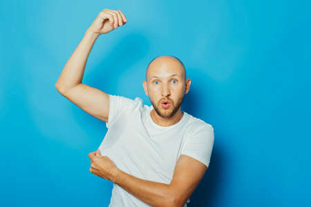 Young man in a white T-shirt with wet armpits from sweat on a blue background. Concept of excessive sweating, heat, deodorant.