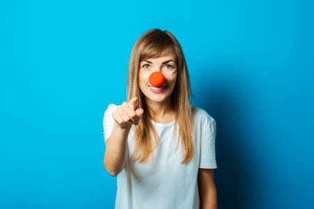 Beautiful young woman in a white T-shirt and a red clown nose smiles and points a finger on a blue background. Concept party, costume, red nose day.