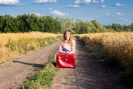 Beautiful young woman sits on a suitcase along the road between the wheat fields in the background. Travel concept, vacation.