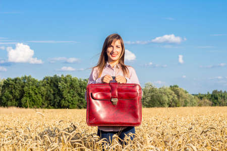 Beautiful young woman with a suitcase on a wheat field. Travel, vacation concept.