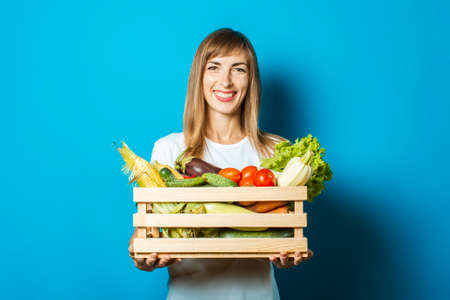 Young woman holds a box with fresh vegetables on a blue background. Good harvest concept, natural product.